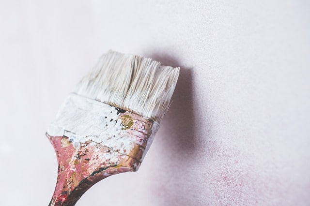 paint brush coloring the wall with white paint