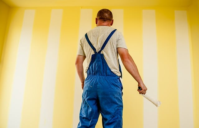 painter holding a paint brush while facing the painted wall