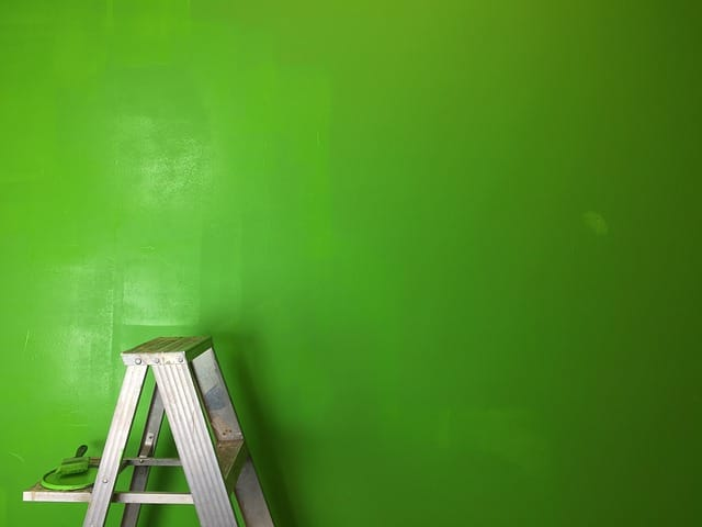 wall is painted with color green paint and a ladder and brush