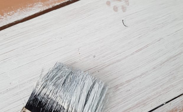 White paint on wooden surface using the paint brush