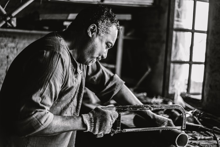 A man cutting a pipe with a saw